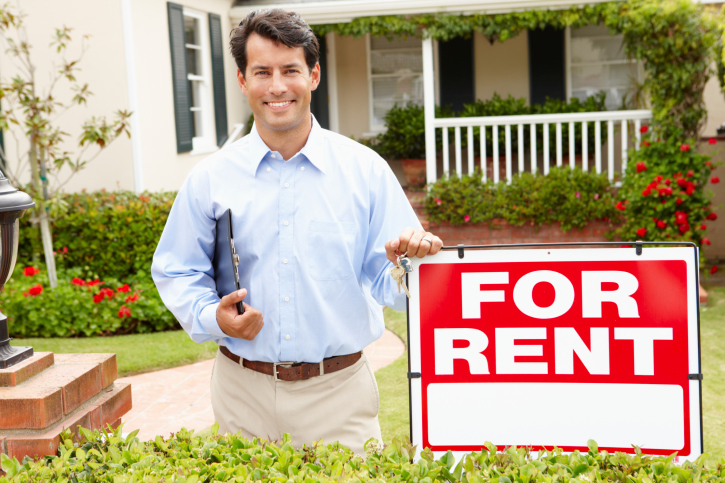 man standing by renting sign